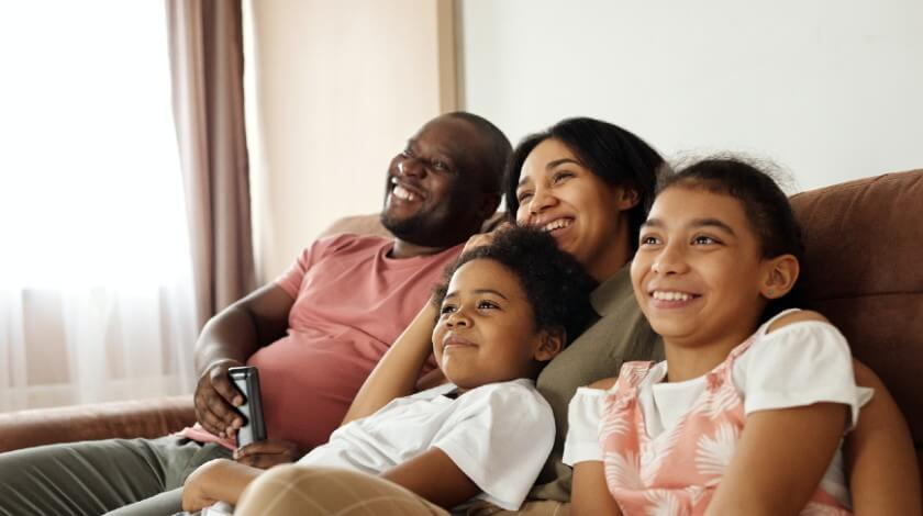 A family laughing together on the couch