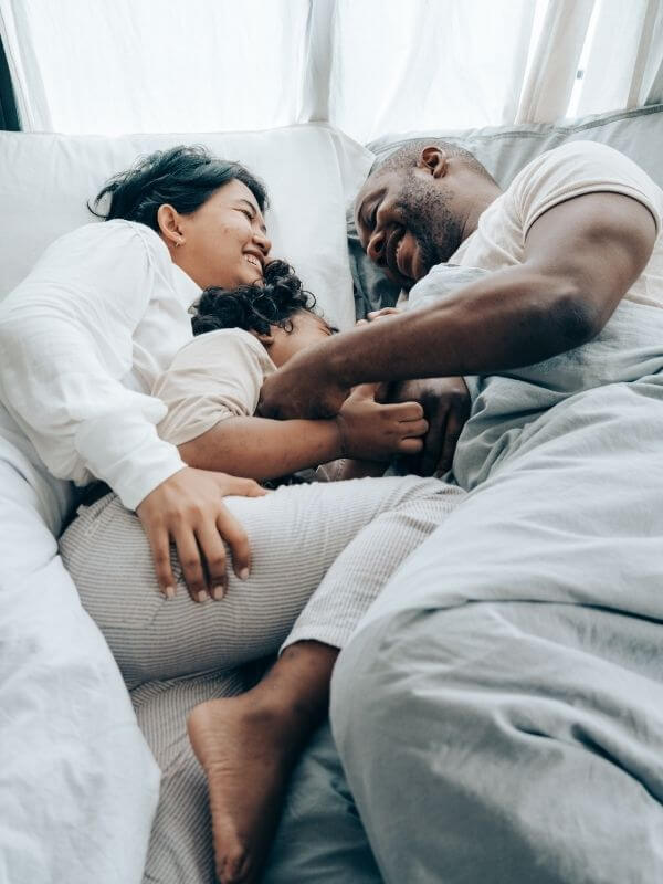 A happy family laying on the bed laughing