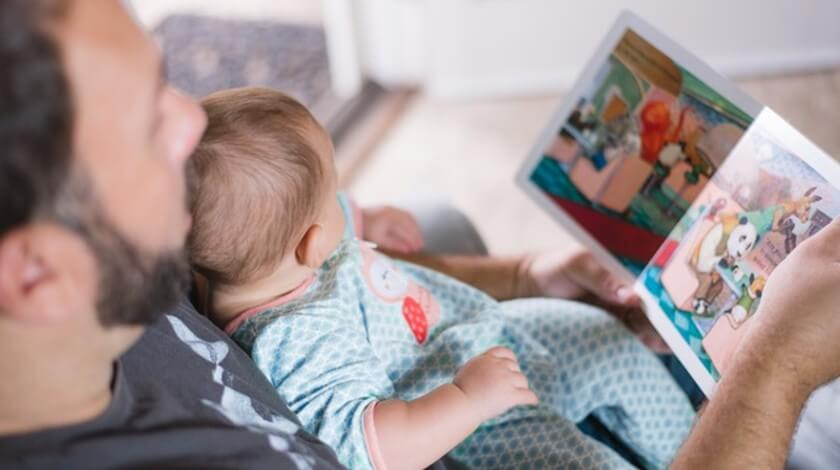 a father holding his baby on the couch while reading a children's book